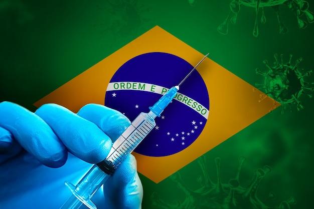 Campagna di vaccinazione brasiliana covid19 la mano in un guanto di gomma blu tiene la siringa davanti alla bandiera