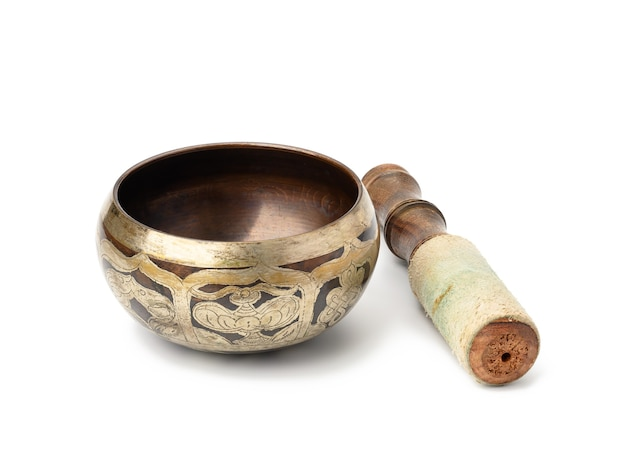 Ciotola di canto d'ottone e maglio di legno isolato su superficie bianca. strumento musicale per la meditazione, il rilassamento, varie pratiche mediche legate ai bioritmi, nello yoga