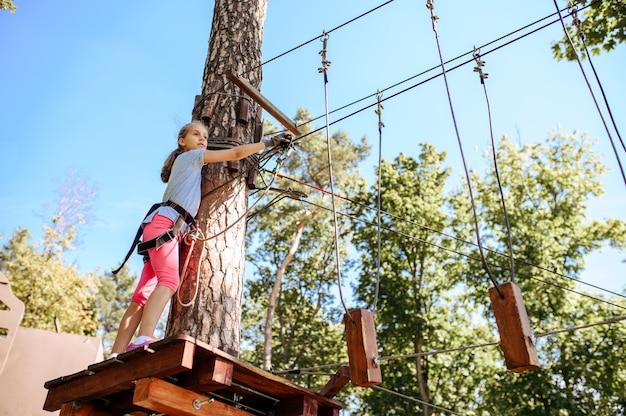 Bambini coraggiosi in attrezzatura si arrampica nel parco avventura, parco giochi. bambini che si arrampicano sul ponte sospeso, avventura sportiva estrema in vacanza, intrattenimento all'aperto