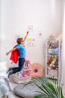 Il ragazzino coraggioso salta giù dal letto, immaginando il volo. il bambino gioca al supereroe