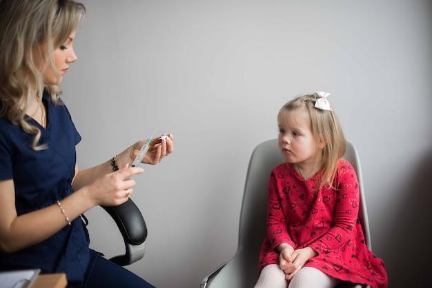 Coraggioso ragazzino bambino ragazza che riceve l'iniezione in ufficio medici
