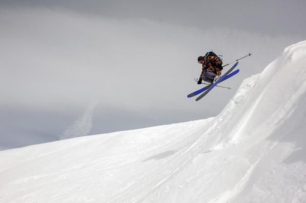 Lo sciatore coraggioso decolla da terra mentre scivola giù per le montagne innevate