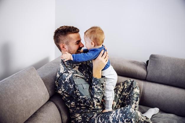 Coraggioso soldato in uniforme seduto sul divano in soggiorno e tenendo in braccio il suo amato unico figlio. il bambino è felicissimo e abbraccia suo padre.