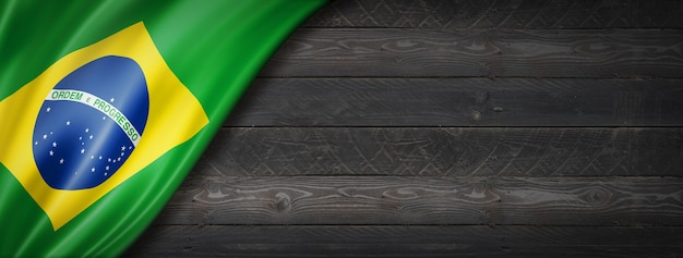 Bandiera del brasile sul muro di legno nero. banner panoramico orizzontale.
