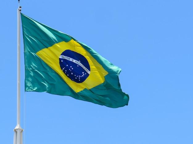 Bandiera del brasile che fluttua nel vento al centro della bandiera con le parole ordine e progresso