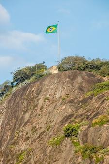 Bandiera del brasile in cima alla pietra del timone a rio de janeiro in brasile.