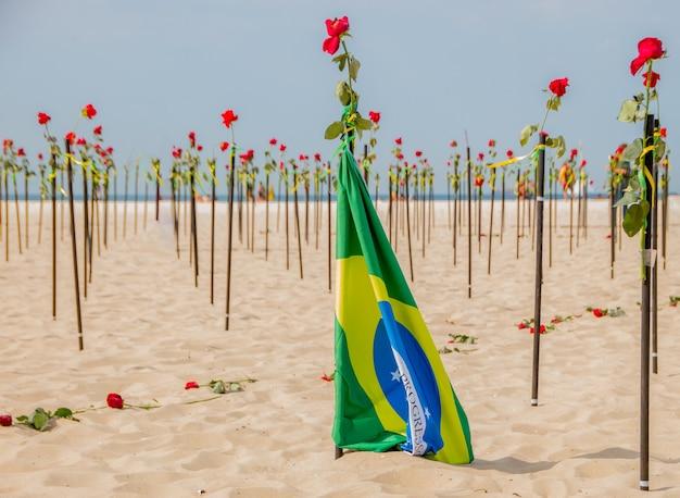 Bandiera del brasile con rose sullo sfondo sulla spiaggia di copacabana a rio de janeiro in brasile.