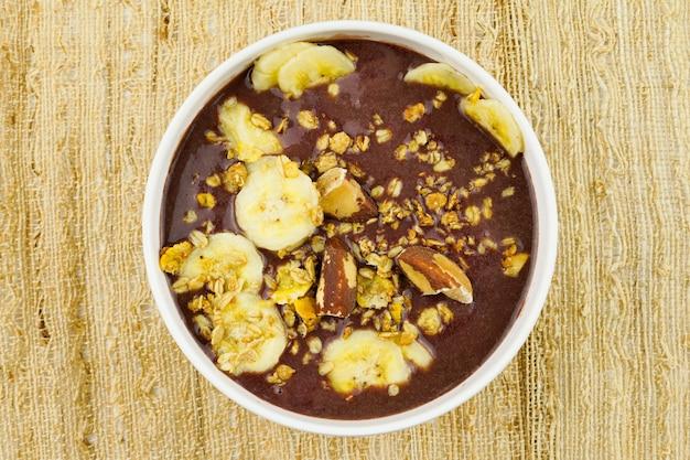 Aãƒâ§ai brasiliano in una ciotola bianca con banana, muesli e castagne.