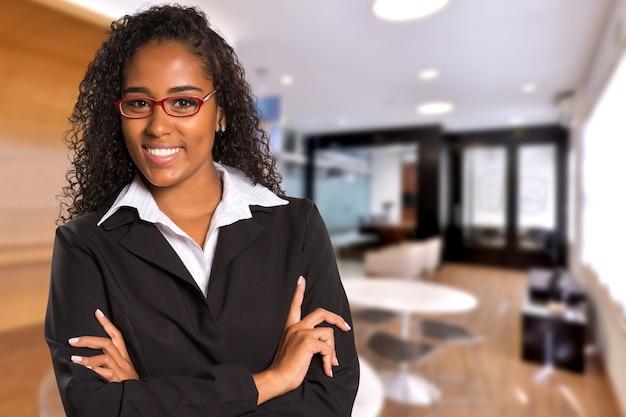 Donna nera brasiliana di affari che guarda l'obbiettivo su spazio ufficio offuscata. copia spazio.