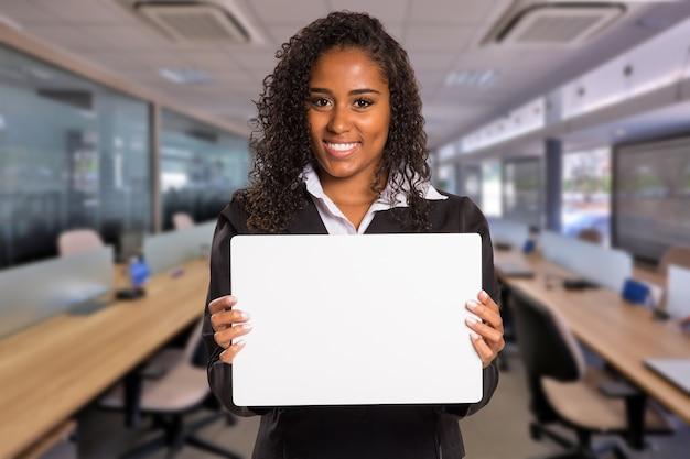 Donna d'affari nera brasiliana con carta bianca in mano che guarda l'obbiettivo su spazio ufficio offuscata. copia spazio.
