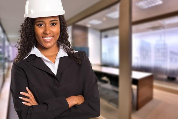 Donna nera brasiliana dell'ingegnere che guarda l'obbiettivo su spazio ufficio offuscato. copia spazio.