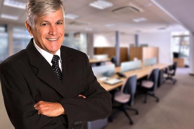 Uomo d'affari brasiliano che guarda l'obbiettivo nello spazio ufficio sfocato. copia spazio.
