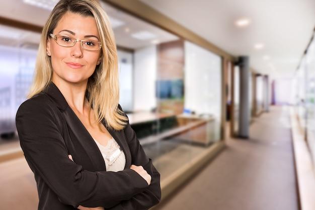 Donna brasiliana di affari che guarda l'obbiettivo nello spazio ufficio sfocato. copia spazio.
