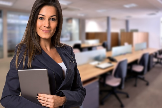 Donna brasiliana di affari con la compressa che guarda l'obbiettivo nello spazio ufficio sfocato. copia spazio.