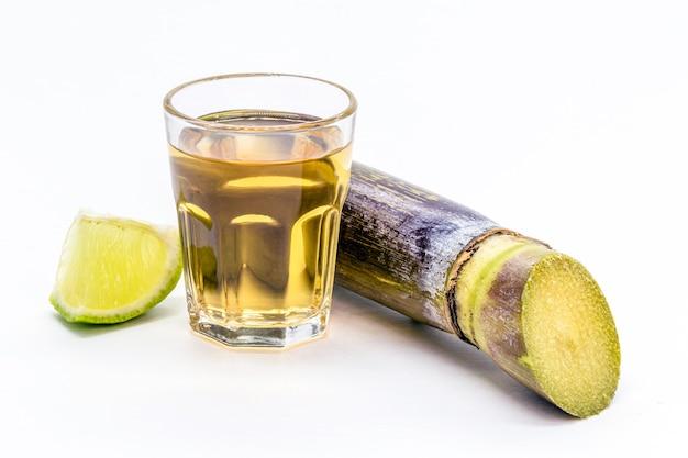 Coppa cachaã§a brasiliana su sfondo bianco isolato con canna da zucchero sul lato.