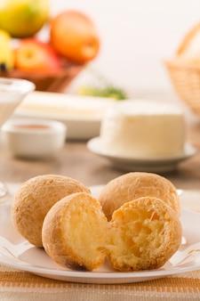 Panini al formaggio brasiliano. tavolo bar al mattino con pane al formaggio e frutta.
