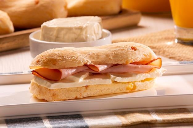Panini al formaggio brasiliano con formaggio e prosciutto. caffè da tavola al mattino con pane al formaggio.