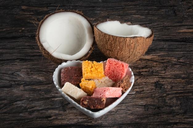 Caramelle brasiliane al cocco in un cesto a forma di cuore su uno sfondo di legno rustico