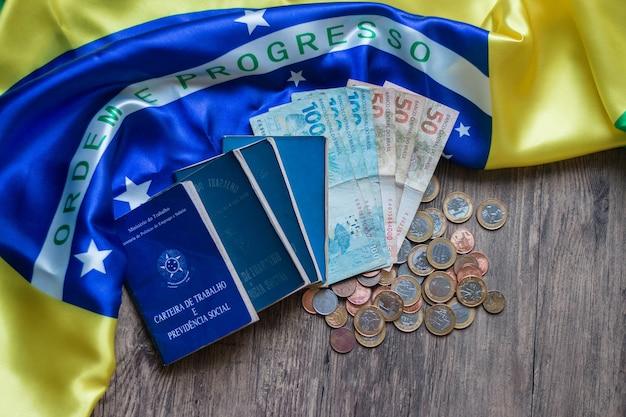 Documento brasiliano e documento di sicurezza sociale e valuta brasiliana sulla bandiera brasiliana.