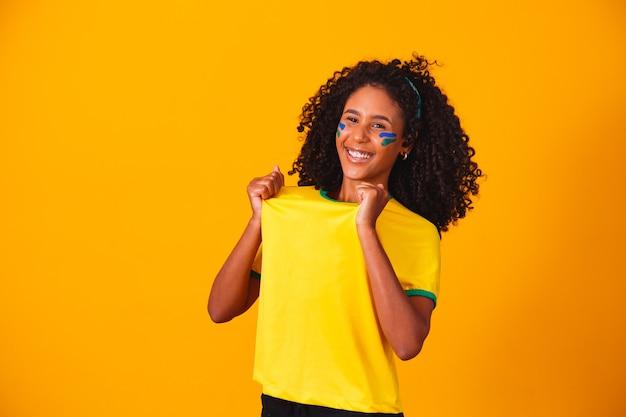 Fan brasiliano. fan brasiliano che celebra il calcio o la partita di calcio. colori del brasile.