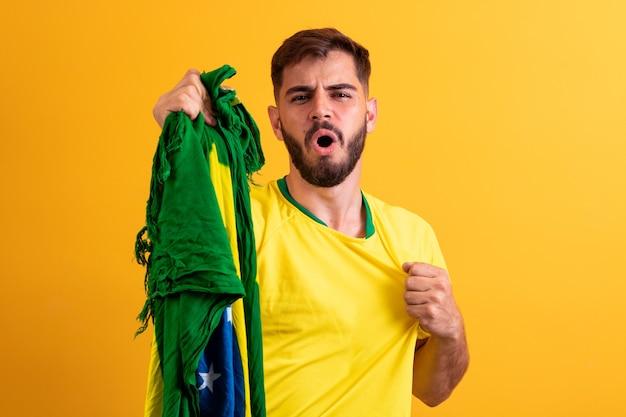 Fan brasiliano che acclamava tra la folla su sfondo giallo.