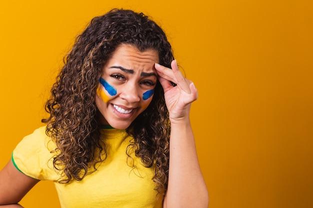Tifoso brasiliano deluso su sfondo giallo con una camicetta brasiliana