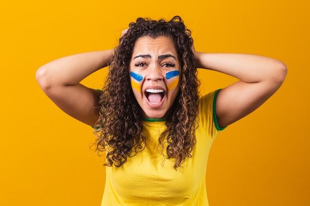 Tifoso brasiliano eccitato e nervoso per la partita su sfondo giallo
