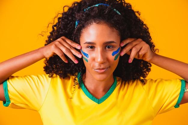 Fan brasiliano. usando la vernice come trucco, fan brasiliano che celebra il calcio o la partita di calcio. colori del brasile.