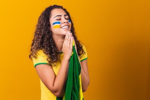 Fan brasiliano con bandiera che prega su sfondo giallo. pregando per il brasile