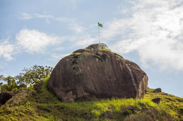 Bandiera brasiliana sulla cima di una roccia a rio de janeiro, brasile.