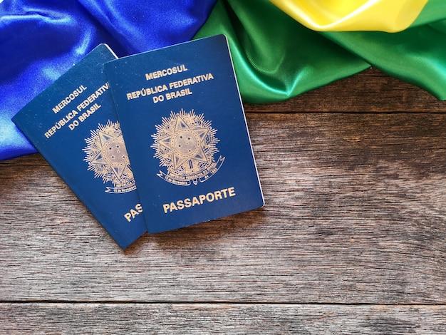 Bandiera brasiliana con passaporto brasiliano e fondo in legno
