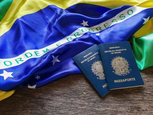 Bandiera brasiliana con passaporto brasiliano e tavolo in legno
