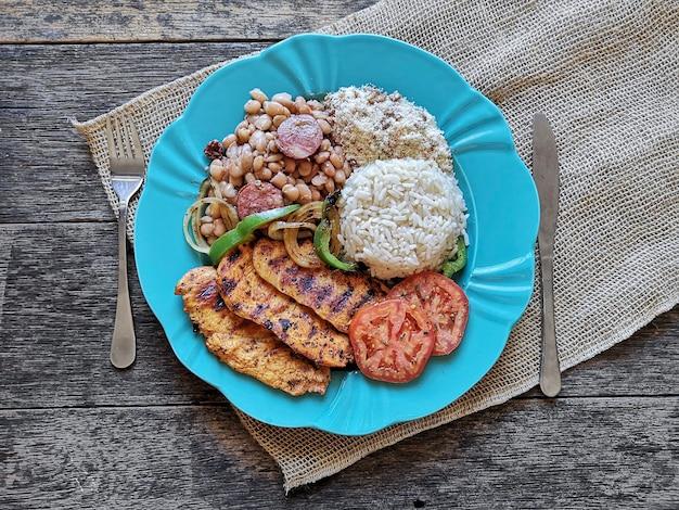 Piatto di cibo brasiliano fagioli, riso, pollo alla griglia e farina.