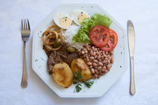 Piatto di cibo brasiliano sul tavolo bianco, vista dall'alto.