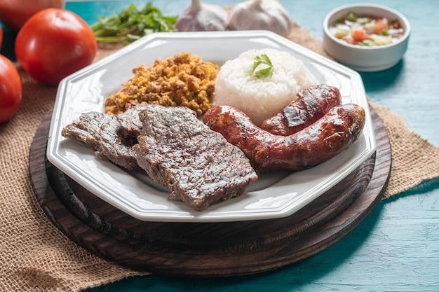 Piatto di cibo brasiliano con barbecue si chiuda.