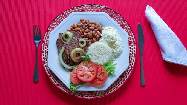 Piatto di cibo brasiliano con vista dall'alto di superficie rossa.