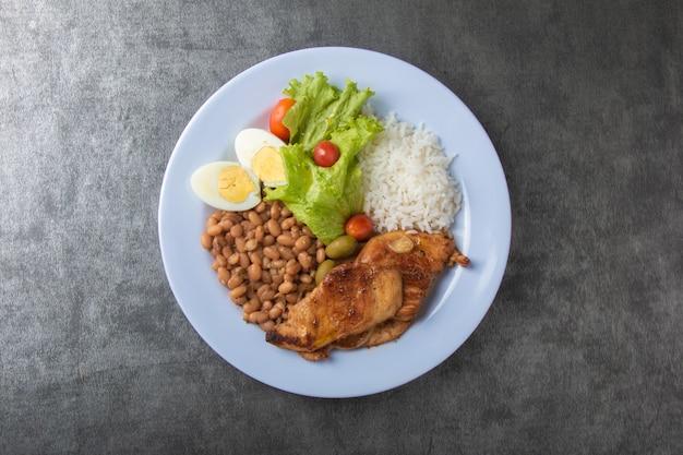 Piatto di cibo brasiliano con fagioli di riso e vista dall'alto di pollo.