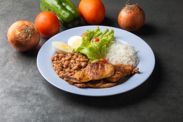 Piatto di cibo brasiliano con fagioli di riso e pollo.