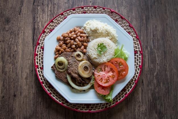 Piatto di cibo brasiliano con vista dall'alto della superficie in legno.