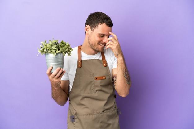 Uomo brasiliano del giardiniere che tiene una pianta sopra fondo porpora isolato che ride
