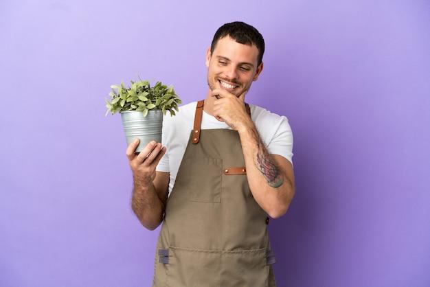 Uomo brasiliano del giardiniere che tiene una pianta sopra fondo porpora isolato che guarda al lato e che sorride