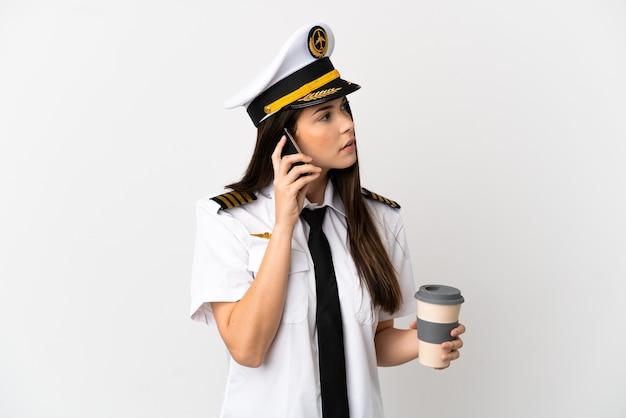 Ragazza brasiliana pilota di aeroplano isolato su sfondo bianco tenendo il caffè da portare via e un cellulare
