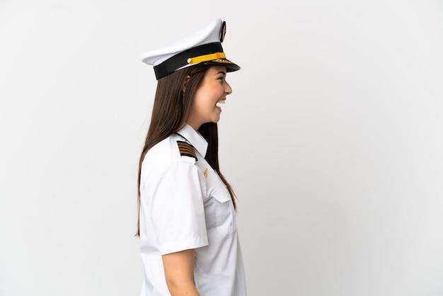 Ragazza brasiliana pilota di aeroplano su sfondo bianco isolato ridendo in posizione laterale