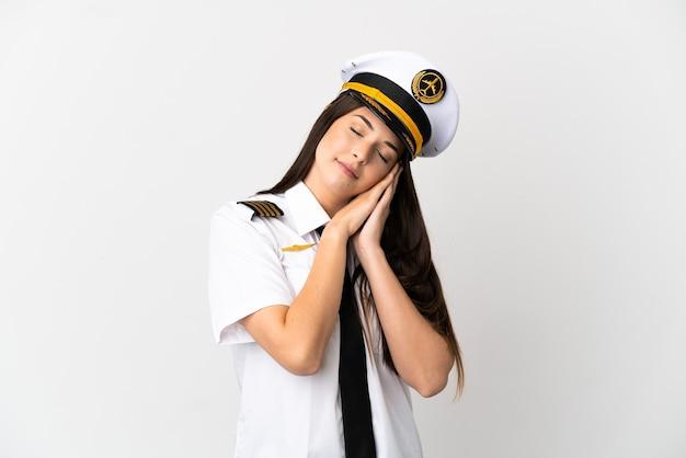 Ragazza brasiliana pilota di aeroplano su sfondo bianco isolato facendo gesto di sonno in espressione adorabile