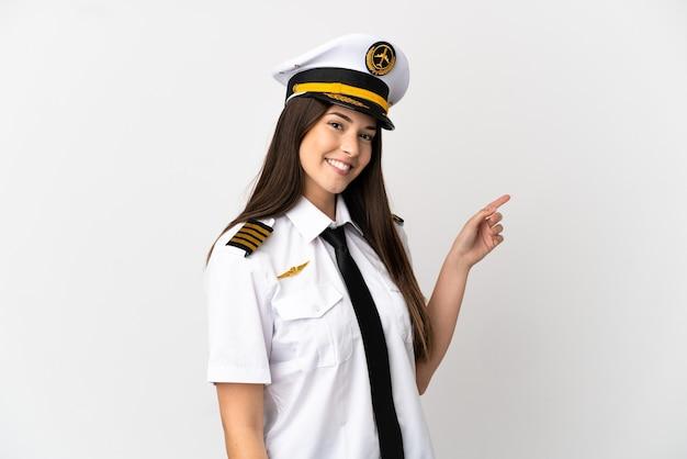 Ragazza brasiliana pilota di aeroplano su sfondo bianco isolato che punta il dito sul lato