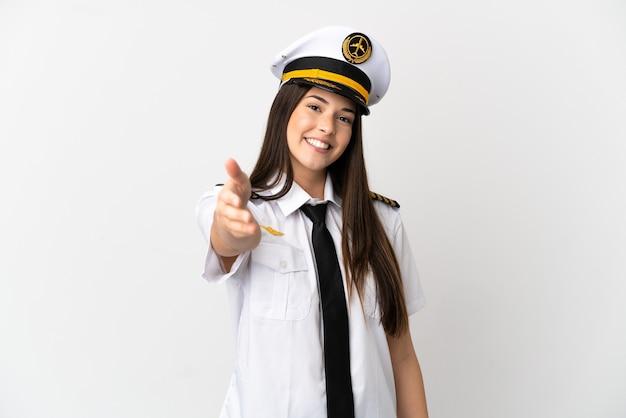 Ragazza brasiliana pilota di aeroplano isolato su sfondo bianco stringe la mano per la chiusura di un buon affare