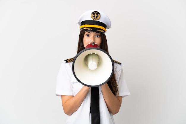 Ragazza brasiliana pilota di aeroplano su sfondo bianco isolato che grida tramite un megafono