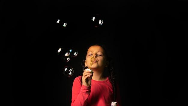 Ragazza brasiliana con la parte superiore rosa che gioca le bolle di sapone