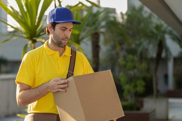 Postino brasiliano che consegna un pacco sulla strada. acquisto via internet consegnato a casa.