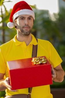 Postino brasiliano vestito da babbo natale che consegna un regalo. acquisto online in fase di consegna.